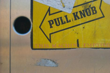 Hole in a wall with a sign that says pull knob.